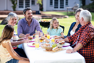 A family dining together outdoors, talking to each other and telling family stories